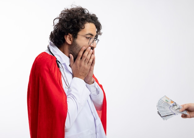 누군가가 빨간 망토 의사 유니폼을 입고 광학 안경에 충격을받은 젊은 백인 남자에게 돈을 건네고 목 주위에 청진기가 복사 공간이있는 흰 벽에 입에 손을 댔다.