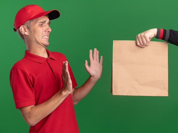 Someone holds out paper package to unpleased young blonde delivery boy standing with raised hands isolated on green wall with copy space