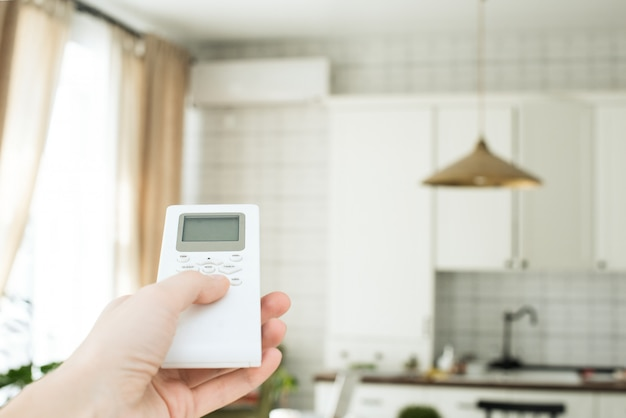 Someone is controlling an air-conditioner's remote
