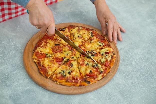 誰かが完成したピザを家族全員のためにセクターのセクションにカットしていますキッチンテーブルのピザのクローズアップ