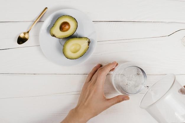 Кто-то наливает воду в стакан, рядом с тарелкой нарезанный авокадо