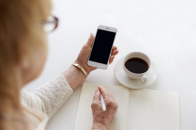 누군가가 커피를 마시면서 전화를 사용하고 있습니다.