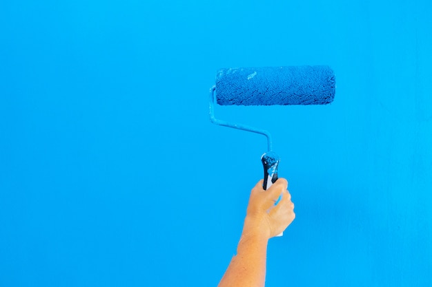 Someone painting wall in a blue color