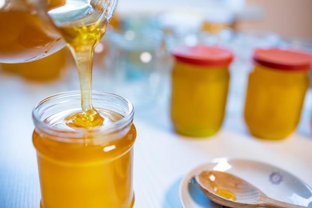 Кто-то разливает мед в прозрачные банки на белом столе