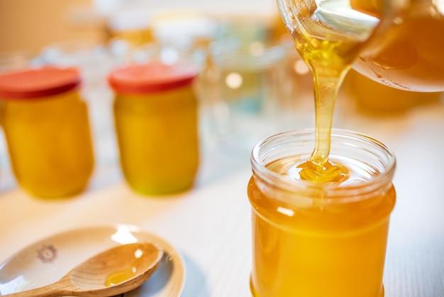 誰かが白いテーブルの上の透明な瓶に蜂蜜を注ぐ