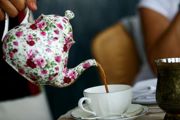 Кто-то наливает чай в чашку из белого фарфора