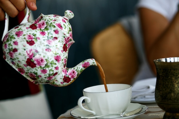 Someone pours tea in white porcelain cup