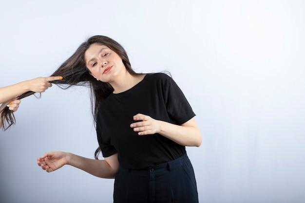 Qualcuno che tira i capelli della ragazza sul grigio.