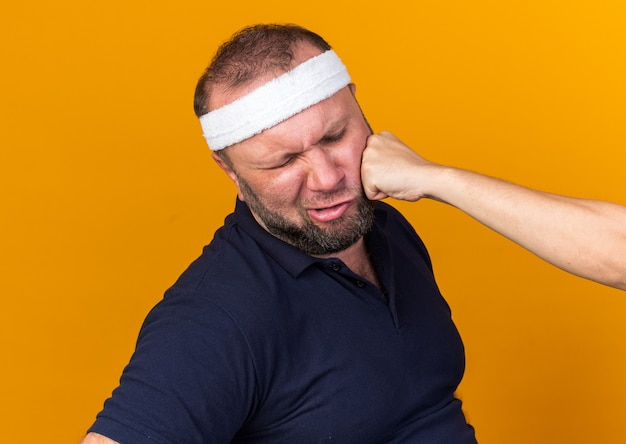 Someone punching in face adult slavic sporty man wearing headband and wristbands isolated on orange wall with copy space