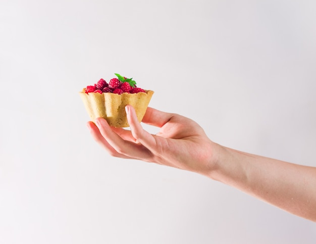 Чья-то рука держит домашнее песочное малиновое тесто. мини-тарталетки «летние ягоды» с ванильным заварным кремом и листьями мяты. свежие десерты на белом фоне изолированы. бесплатная копия пространства.