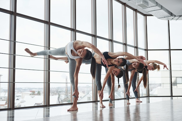 Someone's have good stretching. group of sportive girls in a spacious gym with big windows have training
