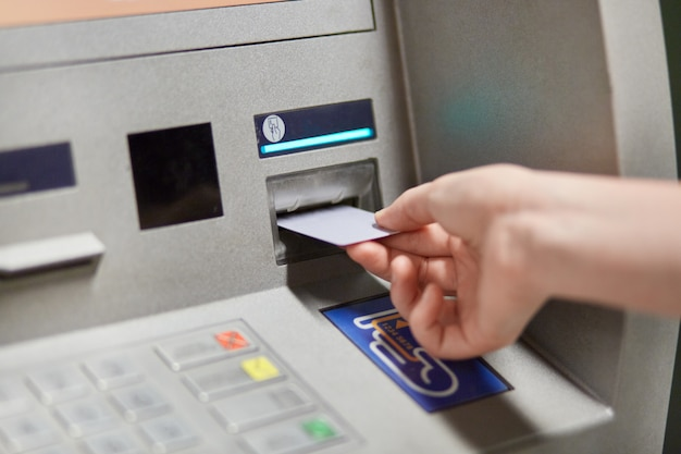 Someone takes off money from outdoor bank terminal, inserts plastic credit card in atm machine, going to withdraw money and get salary