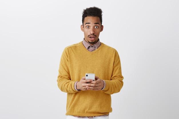 誰かが彼の電話をハッキングしようとしました。灰色の壁にびっくりしている驚きの表情を見つめて、スマートフォンを保持している流行の服でアフロの髪型でショックを受けたハンサムな男