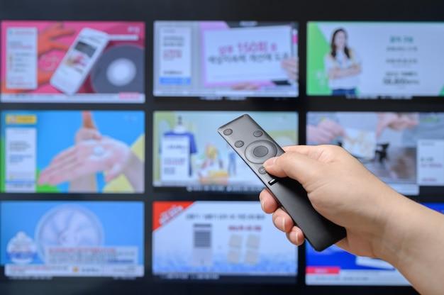 リモコンを手に持ってテレビのホームショッピングチャンネルを検索する人。