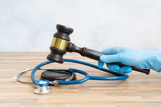 Someones hand with law gavel in hand, medical law concept