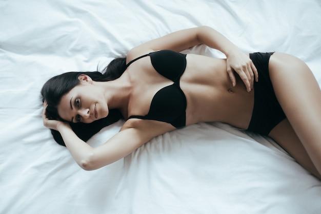 彼女の心に何かクレイジーなもの。黒のランジェリーで魅力的な若い女性の上面図