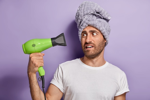 電気ヘアドライヤーに問題があります。欲求不満の男は髪を乾かし、頭にタオルを着て、朝に美容トリートメントをします