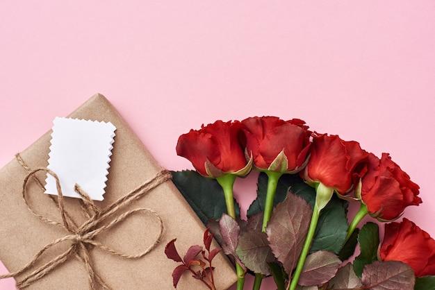 Что-то особенное для ее букета из свежих красных роз и домашнего подарка в крафт-упаковке.