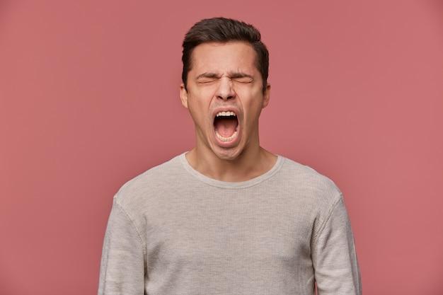 何か問題でも!若い魅力的な男のクローズアップは、空白の長袖を着て、目を閉じて叫んでピンクの背景の上に立って、怒って不幸に見えます。
