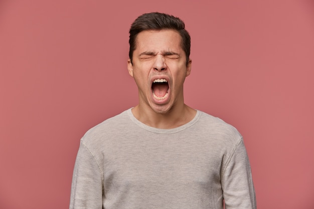 Something wrong! close up of young attractive guy wears in blank long sleeve, stands over pink background with closed eyes and screaming, looks angry and unhappy.