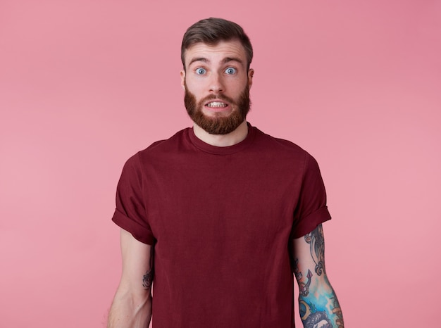 Something wrong! young attractive tattooed red bearded man in blank t-shirt, looks shocked and sad, stands over pink background.