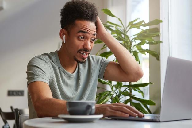 何か問題でも!若いは魅力的な浅黒い肌の少年を不思議に思って、カフェに座ってラップトップで働き、頭を抱えてショックを受けた表情でモニターを見ています。