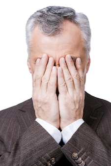 Sometimes there are situations that are out of control.  frustrated mature man covering his face by hands while standing against white background