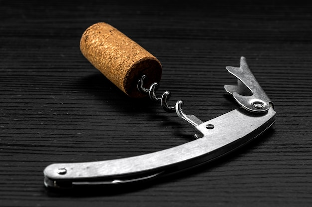 Sommelier corkscrew with a stopper that has just been removed from the wine bottle, on black wooden
