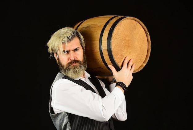Сомелье рассматривает вино. бочка вина. бармен в погребе с изысканным напитком. опытный сомелье продегустирует вино. бармен дегустирует вино на дегустации. мужчина-сомелье ценит напиток.