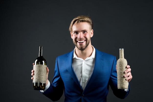 Сомелье держит две бутылки вина. концепция профессиональной дегустации вин. деловой костюм человека с винными бутылками в руках. сомелье красивый веселый парень на темном фоне. какое вино тебе нравится.