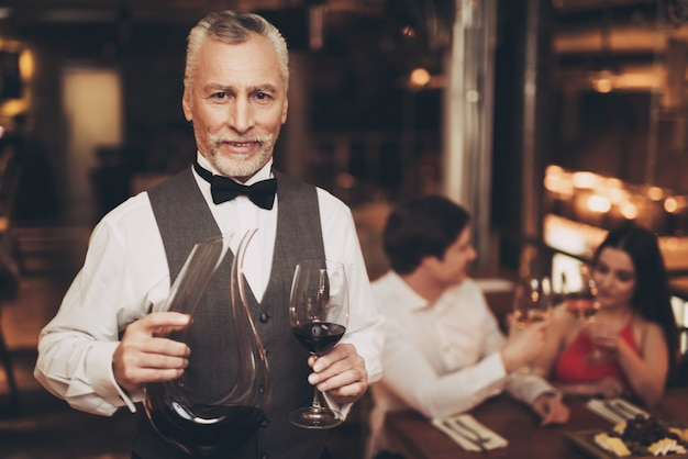 Sommelier is holding glass of wine and decanter.