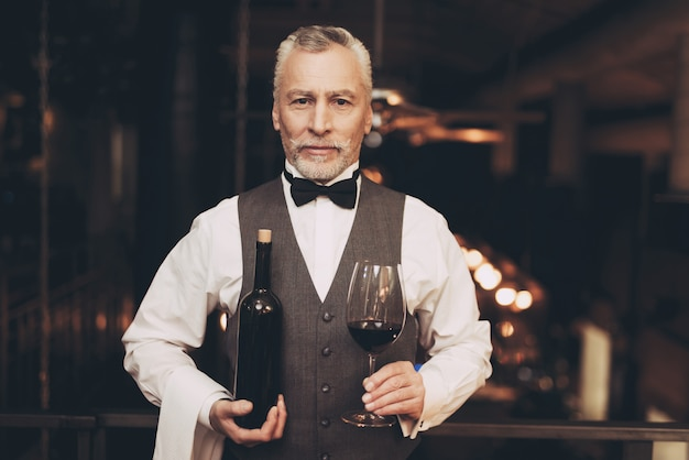 Sommelier is holding wine in glass and bottle