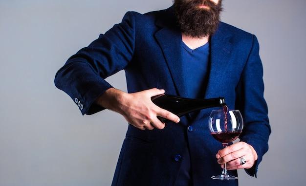 Мужчина-сомелье, дегустатор, винодельня, мужчина-винодел. бутылка, бокал для красного вина.