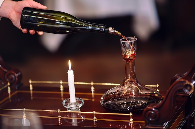 A sommelier pouring red wine into decanter