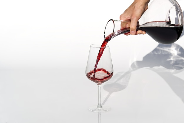 Sommelier pours red wine from decanter to wineglass on white background