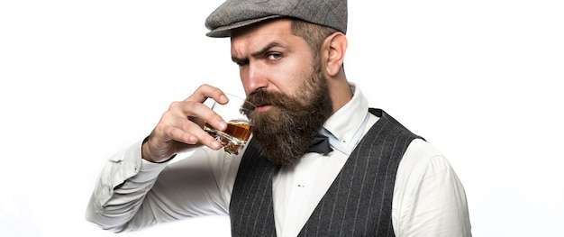 Sommelier tastes expensive drink. handsome well-dressed man in jacket with glass of beverage. bearded man wearing suit and drinking whiskey, brandy, cognac. bearded in is holding a glass of whiskey.