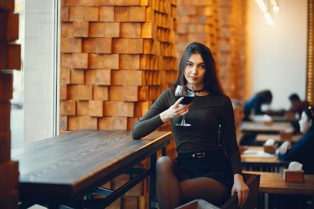 Сомелье дегустирует красное вино. закройте вверх по портрету элегантной женщины с красными губами. леди держит стакан с красным вином и смотрит в камеру.