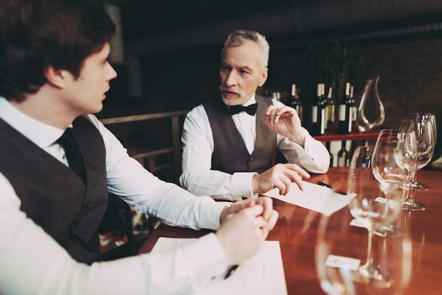 Sommeliers is tasting wine in restaurant.