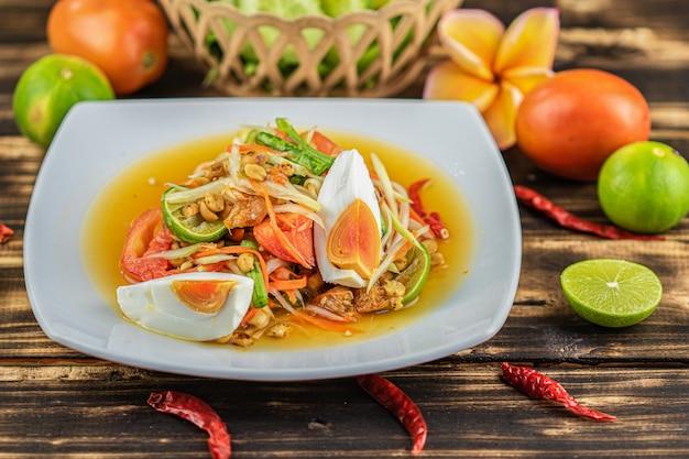 ソムタム。木製のテーブルに塩味の卵とタイのスパイシーグリーンパパイヤサラダ(somtum khai kem)