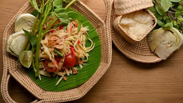 木製のテーブルに野菜ともち米を添えたソムタムまたはパパイヤのサラダタイの伝統的な料理