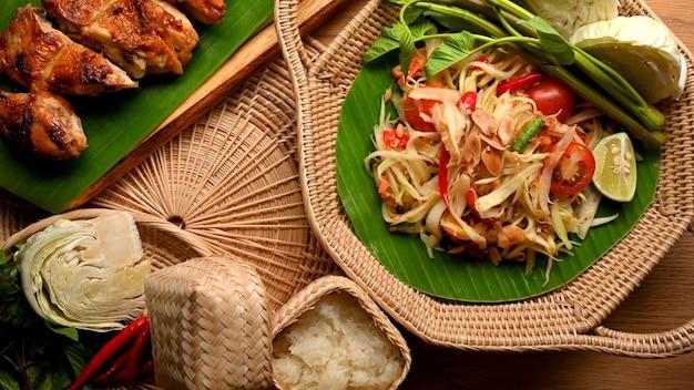 籐のプレートに野菜とタイ風グリルチキンタイ料理を添えたソムタムまたはパパイヤサラダ