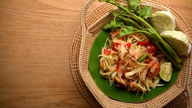 木製のテーブルの籐のプレートに野菜とソムタムまたはパパイヤのサラダタイ料理