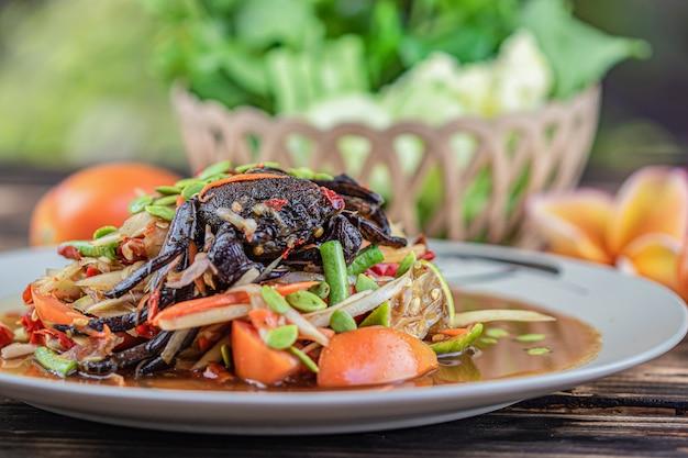 Somtum poo. тайский салат из папайи с соленым крабом и много овощей на фоне деревянный стол.