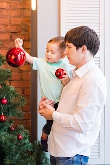 Сын и папа украшают елку дома в гостиной.