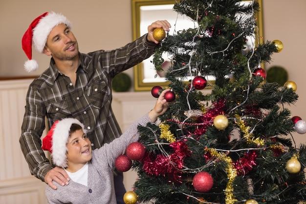 息子とクリスマスツリーを飾るお父さん