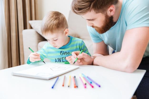息子とお父さんが一緒に座ってテーブルに描いています