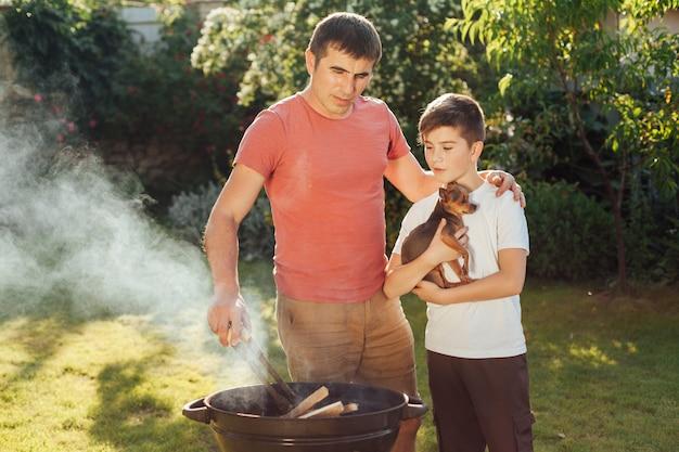 息子と父親がピクニックで一緒に食べ物を準備します。