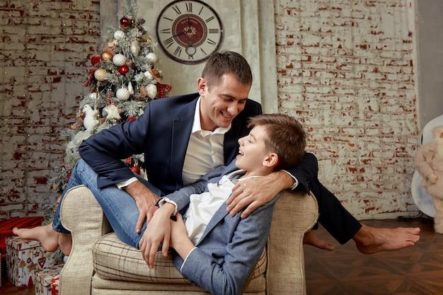 Сын и папа радуются на фоне новогодних украшений. сын и отец сидят в кресле и радостно болтают в канун рождества.