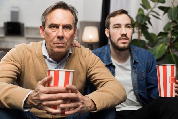 Сын и отец смотрят телевизор в гостиной
