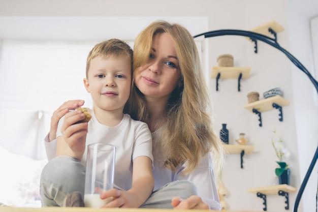 息子とお母さんはミルクを飲みます。母親は朝食前に赤ちゃんを抱きしめます。